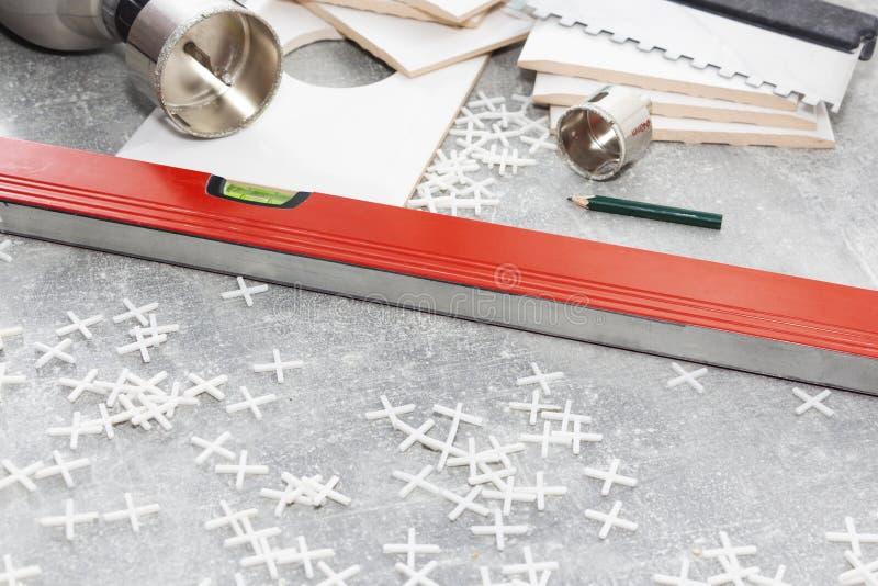 Keramiska tegelplattor och hjälpmedel för tileren, tegelplattainstallation Hemförbättring renovering - bindemedel för golv för ke arkivfoton