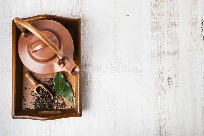 Keramiska tekanna och teblad arkivfoto