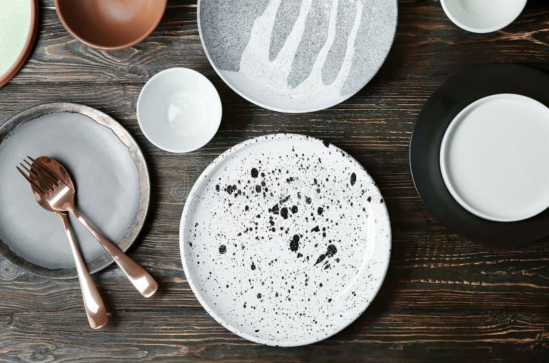 Keramiskt bordsservis och bestick på träbakgrund arkivbilder