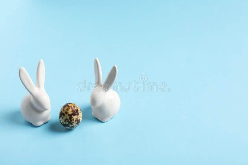 Keramiskt påskkaniner och ägg på färgbakgrund royaltyfria bilder