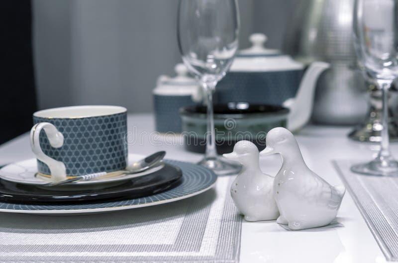Keramiskt salta shaker i form av änder i inre av en modern matsal royaltyfri fotografi