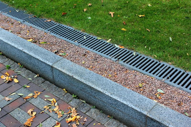 Kerbside and rainwater drainage system in a park stock for Rain drainage system