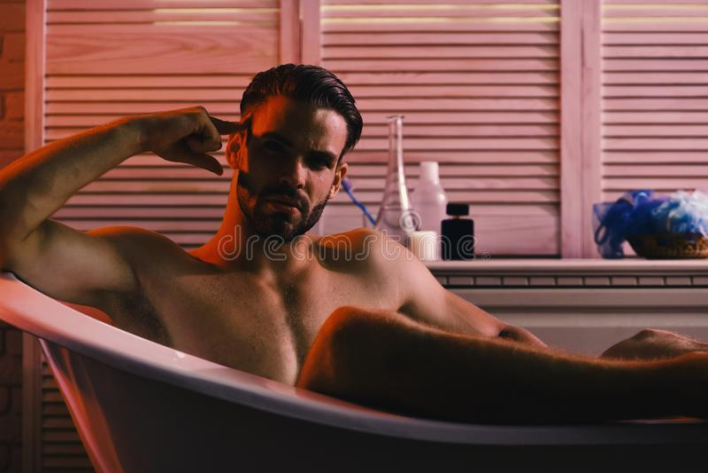 Kerel in badkamers met toiletries op achtergrond, selectieve nadruk Geslacht en eroticaconcept: machozitting naakt in badkuip royalty-vrije stock afbeelding