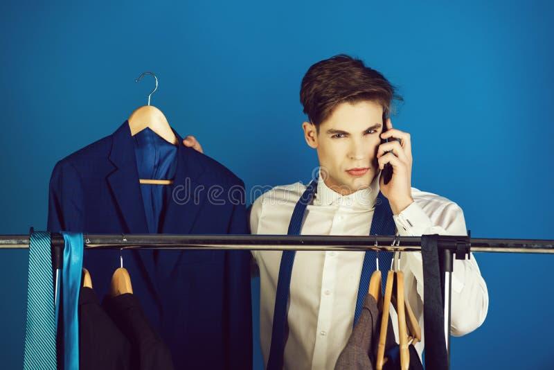 Kerel bij garderobehanger die op telefoon spreken royalty-vrije stock fotografie