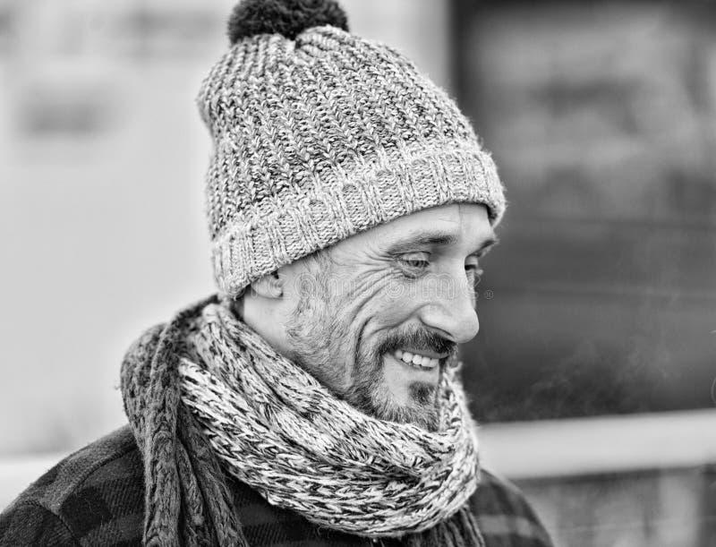 Kerel in de winterhoed en sjaal Portret van de glimlachende mens op straat in zwart-wit royalty-vrije stock afbeelding