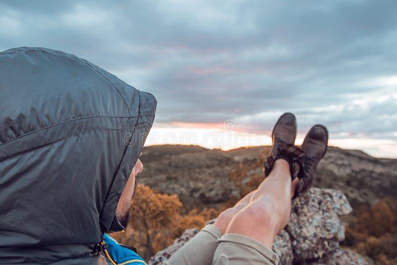 Kerel die in de bergen rusten Bergbeklimmer die het landschap waarnemen stock afbeeldingen