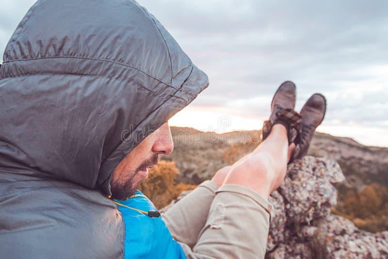 Kerel die in de bergen rusten Bergbeklimmer die het landschap waarnemen royalty-vrije stock afbeeldingen