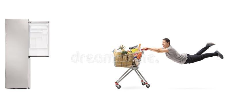 Kerel die door boodschappenwagentje naar een lege koelkast worden getrokken stock foto