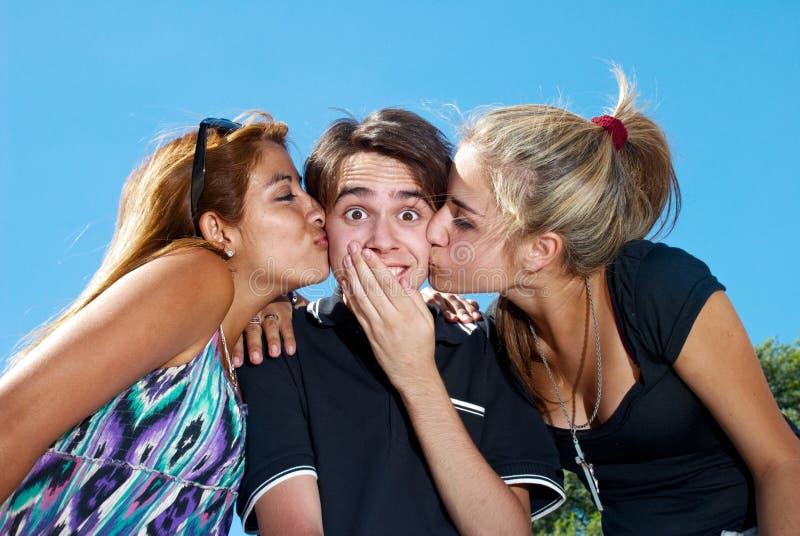 Kerel die door twee aantrekkelijke meisjes wordt gekust stock foto's
