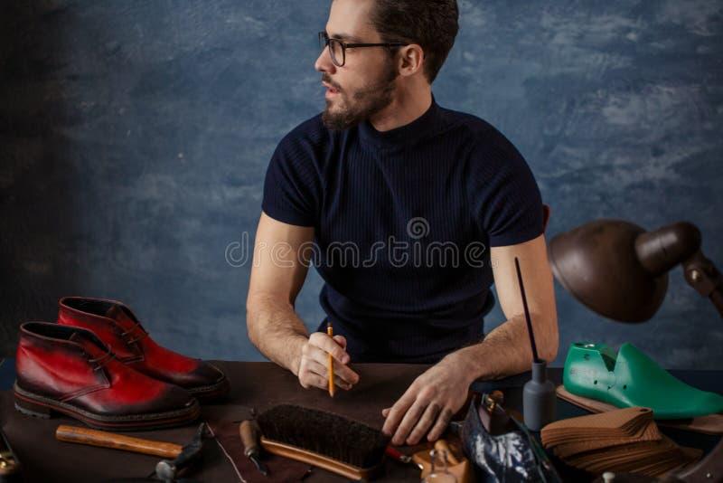 Kerel die in een schoenhandel werken stock fotografie