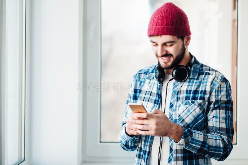 Kerel die een telefoon met behulp van om te luisteren muziek stock fotografie
