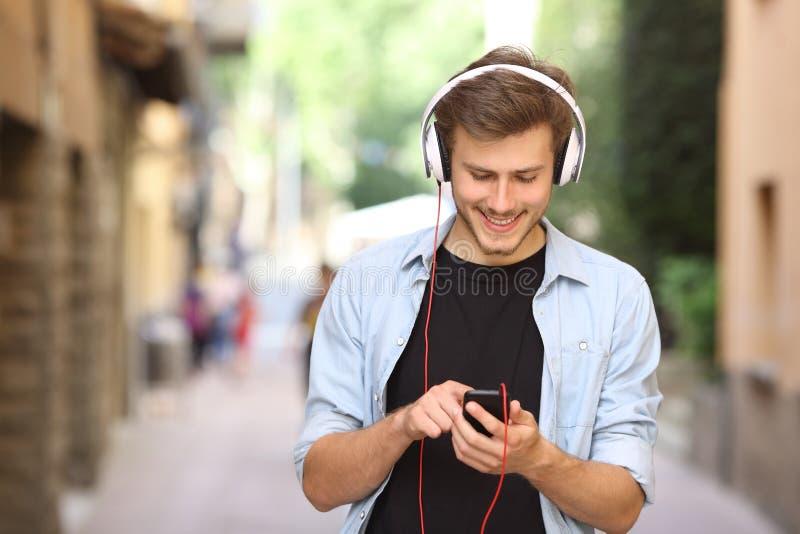 Kerel die en een slimme telefoon met hoofdtelefoons lopen met behulp van royalty-vrije stock afbeeldingen