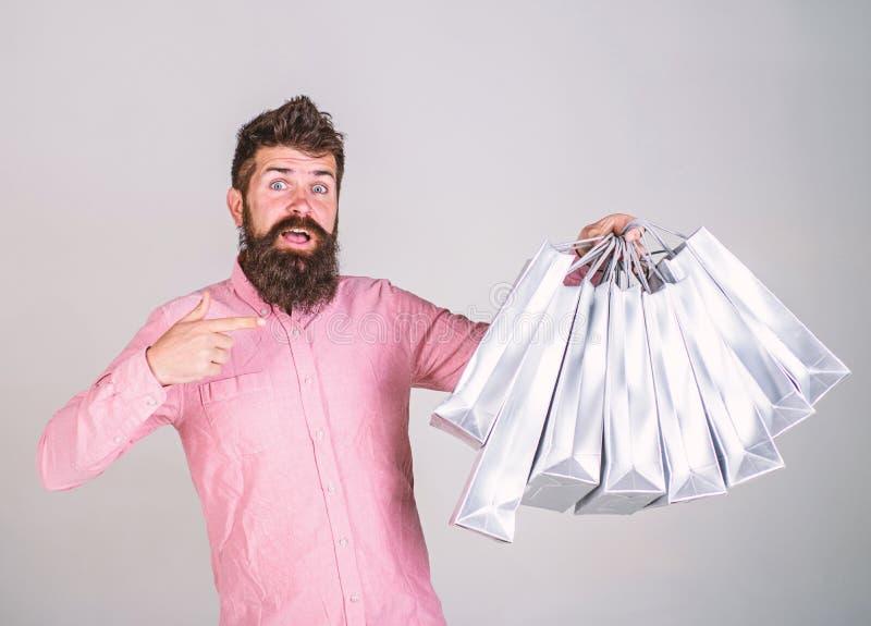 Kerel die en op zakken winkelen richten Aanbevelingsconcept Hipster op verrast gezicht adviseert te kopen Mens met baard stock afbeeldingen