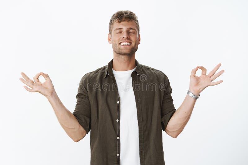 Kerel die gelukkig en ontspannen nirvanagevoel bereiken bevrijd van spanning die met gesloten ogen, brede tevreden glimlach medit stock afbeeldingen