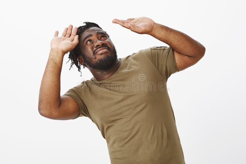 Kerel die gewicht van verantwoordelijkheid proberen te dragen Ontstemd ongemakkelijk donker-gevild mannelijk model in olijft-shir royalty-vrije stock foto's