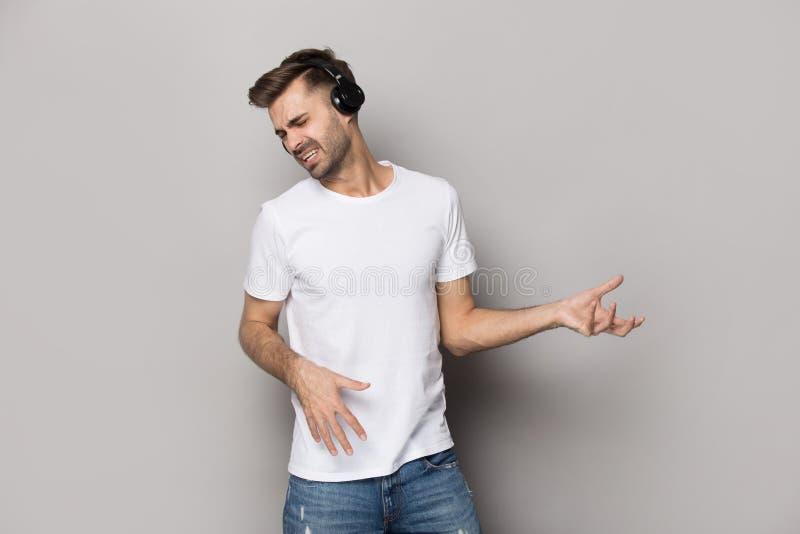 Kerel die hoofdtelefoons dragen die het spelen schot van de gitaar het stellende studio imiteren royalty-vrije stock afbeeldingen