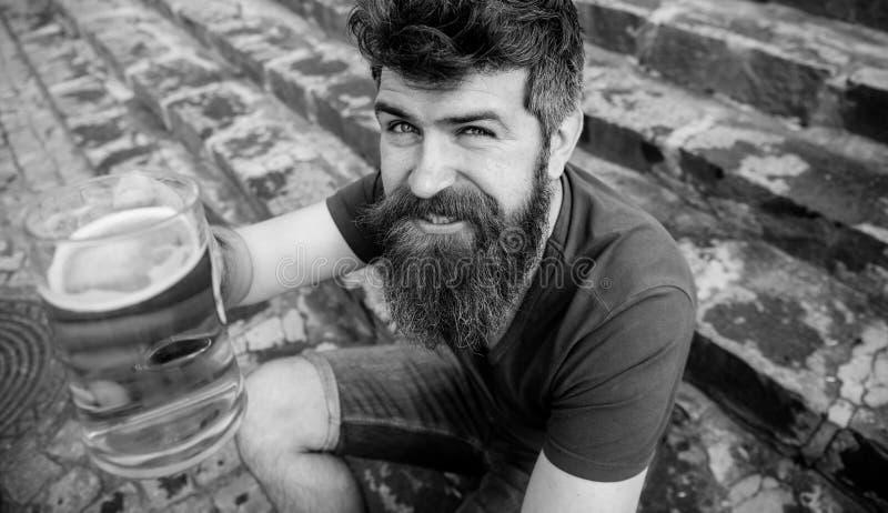 Kerel die op glas met bier van het vat opheffen Hipster op vrolijk gezicht drinkt bier openlucht De mens met baard en snor houdt stock foto's