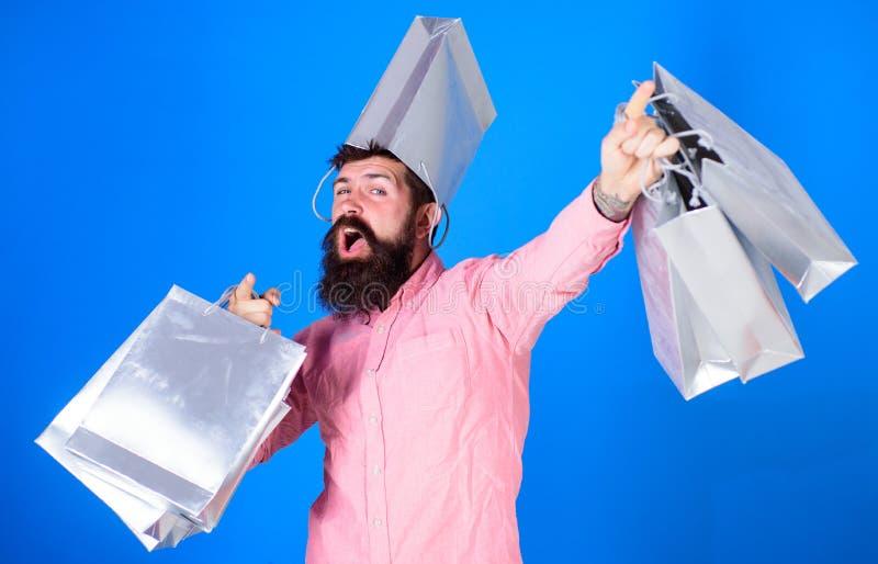 Kerel die op verkoopseizoen winkelen met kortingen Hipster op vrolijk gezicht met zak op hoofd is gewijde shopaholic Mens die met stock afbeeldingen