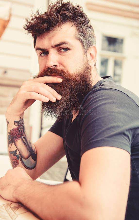 Kerel die rust hebben bij koffieterras Hipster, cliënt, bezoeker op nadenkend gezicht zit bij koffie openlucht Mens met baard en stock fotografie