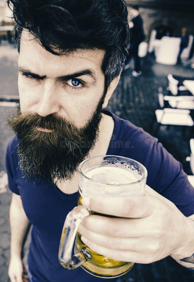 Kerel die rust met koud bier van het vat hebben De mens met baard en snor houdt glas met bier terwijl het ontspannen bij koffiete stock afbeelding