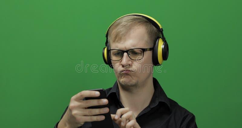 Kerel die smartphone in draadloze gele hoofdtelefoons met behulp van Het groene scherm royalty-vrije stock afbeeldingen