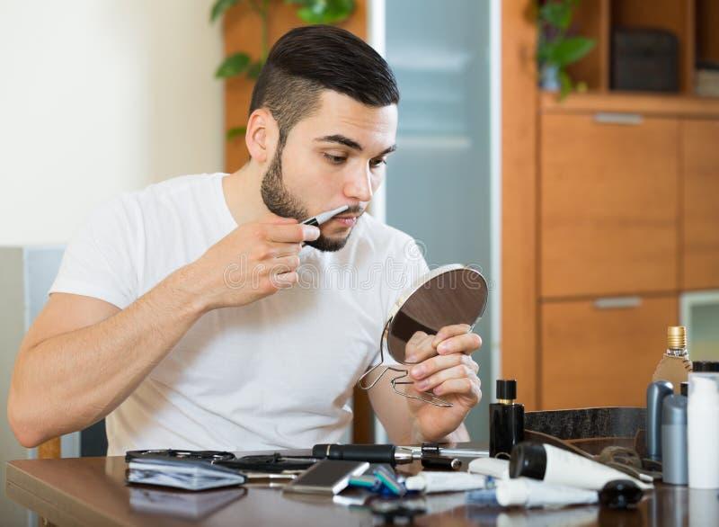 Kerel die spiegel en het scheren baard met snoeischaar bekijken stock foto