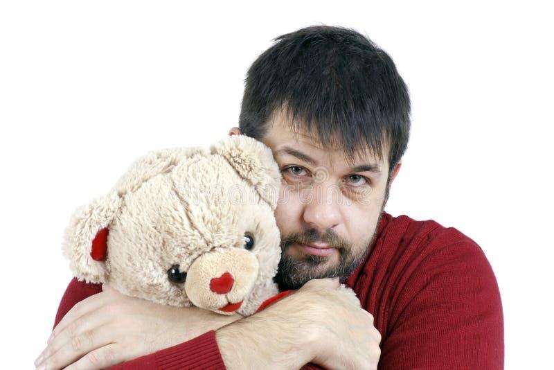Kerel die teddybeer koestert stock foto's