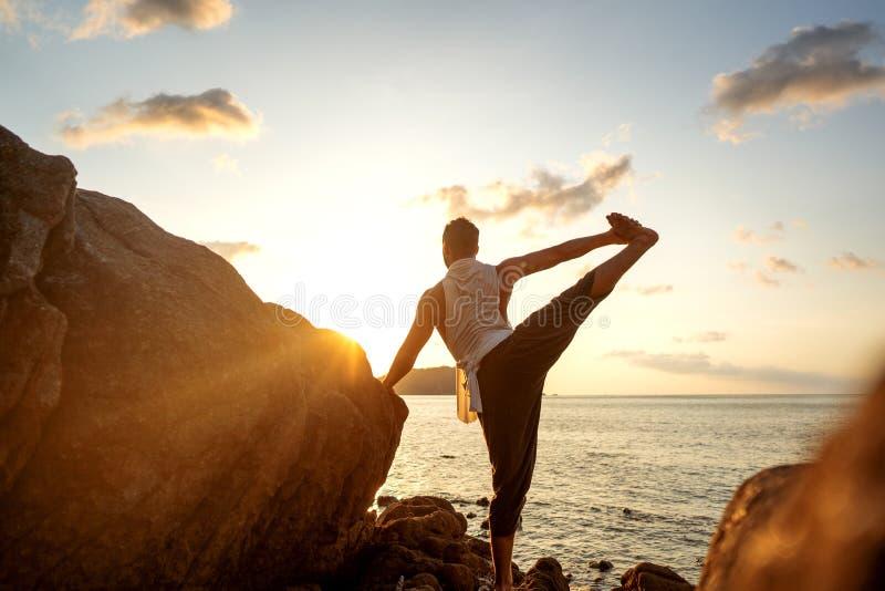 Kerel die yoga doen bij zonsondergang door het overzees royalty-vrije stock foto