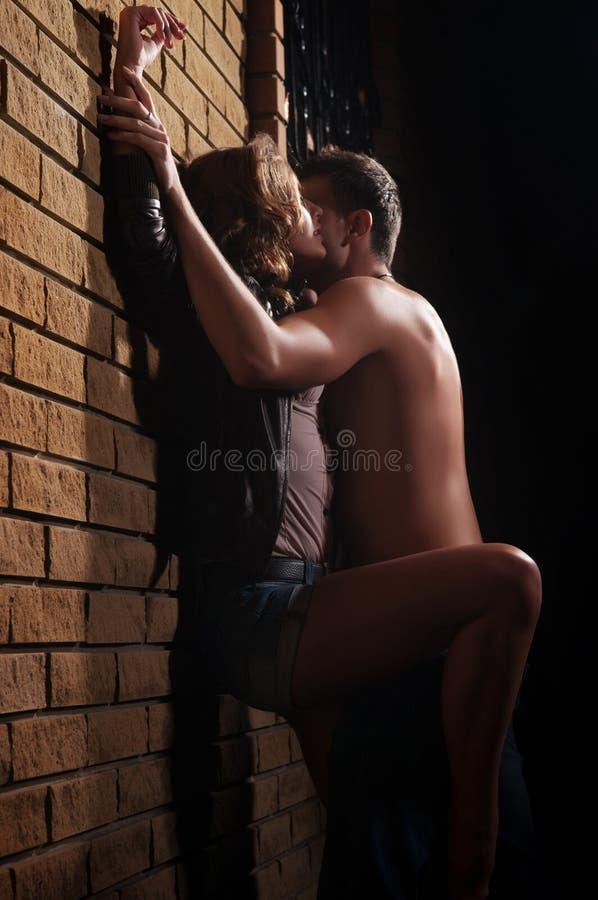 Kerel die zijn meisje thuis kussen tegen een muur royalty-vrije stock fotografie
