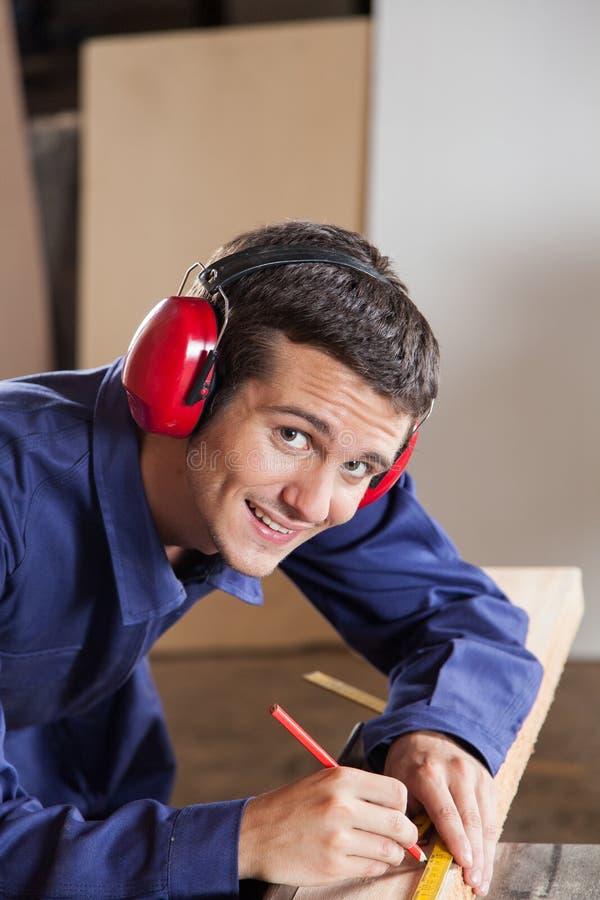 Kerel die in zijn workshop meten royalty-vrije stock afbeelding