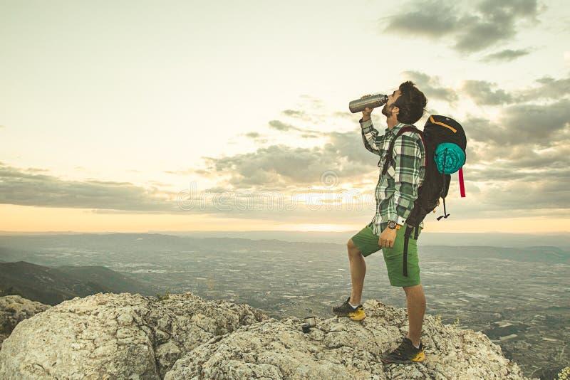 Kerel drinkwater in de bergen royalty-vrije stock afbeelding