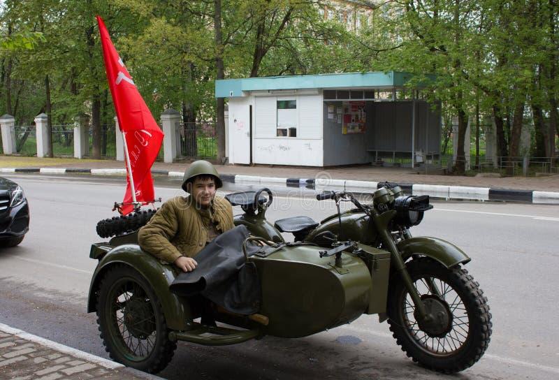 Kerel in een militair uniform van afgelopen jaren op een militaire motorfiets stock foto's
