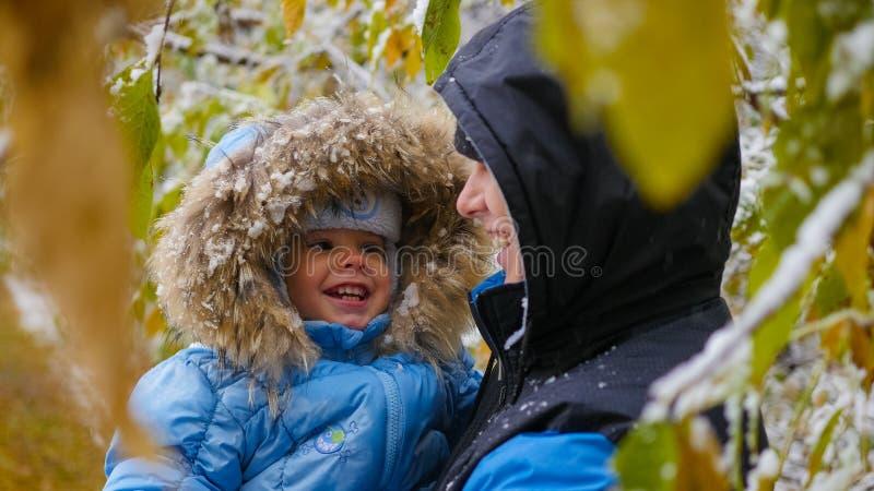 Kerel en kindspelen met een sneeuwboomtak stock fotografie