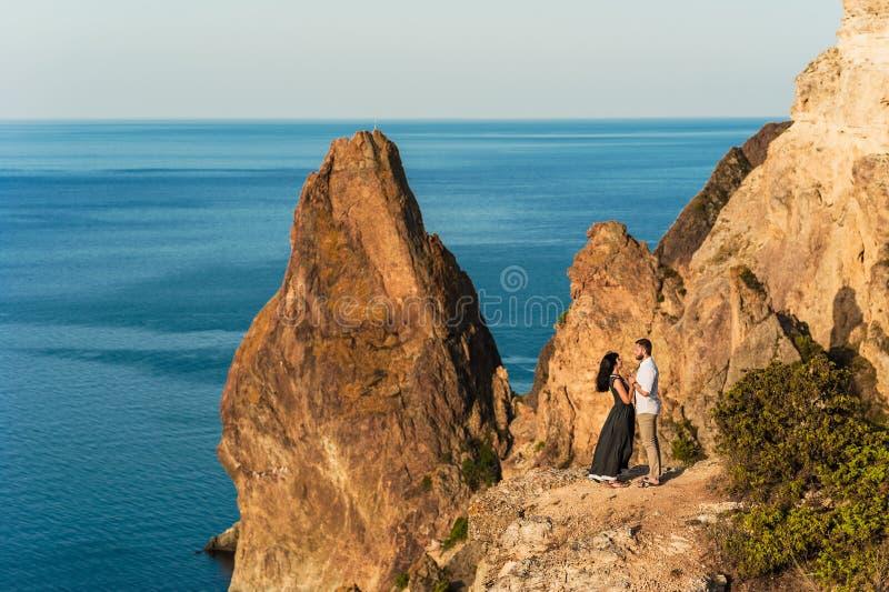Kerel en meisje bij het overzees die op de rand van de klip koesteren royalty-vrije stock foto's