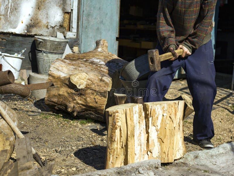 kerel in het dorp die eiken stompen met een wig en een voorhamer, het oogsten hout hakken stock foto