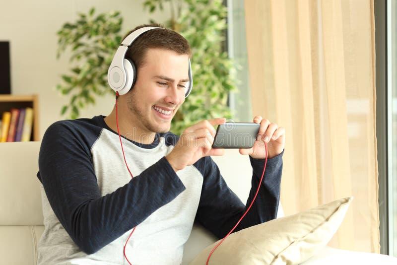 Kerel het luisteren en het letten op media in een smartphone royalty-vrije stock afbeelding