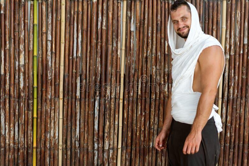 Kerel het stellen op de achtergrond van een bamboemuur in glazen royalty-vrije stock afbeelding