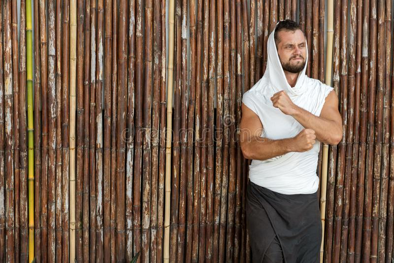 Kerel het stellen op de achtergrond van een bamboemuur in glazen royalty-vrije stock foto's