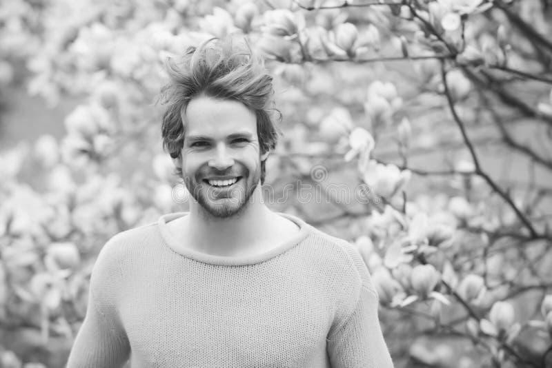 Kerel met baard die in gele sweater op bloemenachtergrond glimlachen stock foto's