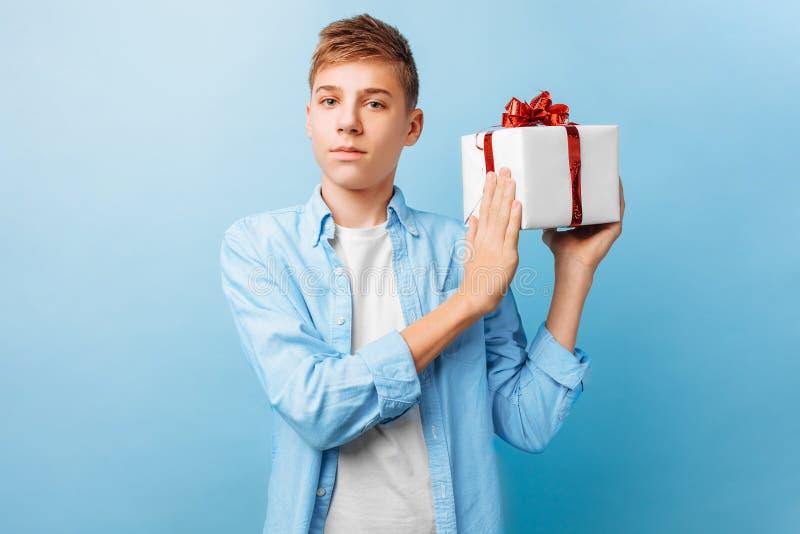 Kerel met een gift in zijn handen voor de Dag van Valentine, op een lichtblauwe achtergrond stock foto's
