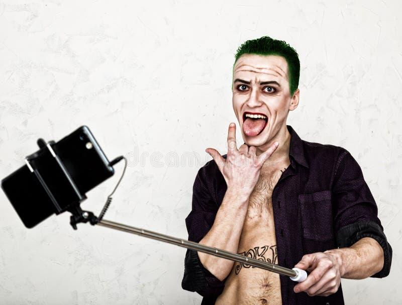 Kerel met gek jokergezicht, groen haar en idiotic glimlach carnaval kostuum het maken van selfy foto royalty-vrije stock afbeelding
