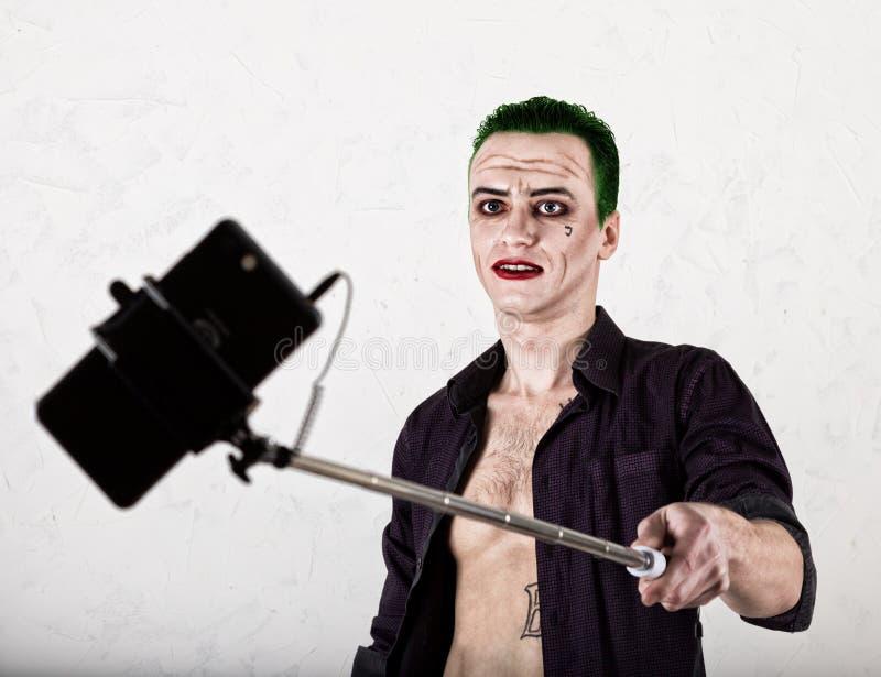 Kerel met gek jokergezicht, groen haar en idiotic glimlach carnaval kostuum het maken van selfy foto stock afbeeldingen