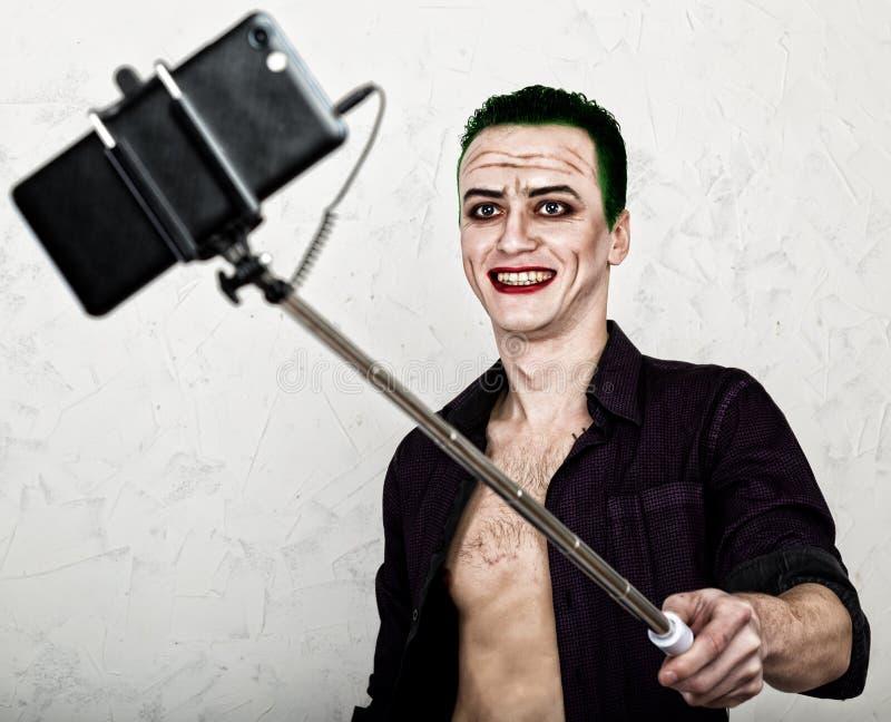 Kerel met gek jokergezicht, groen haar en idiotic glimlach carnaval kostuum het maken van selfy foto royalty-vrije stock foto