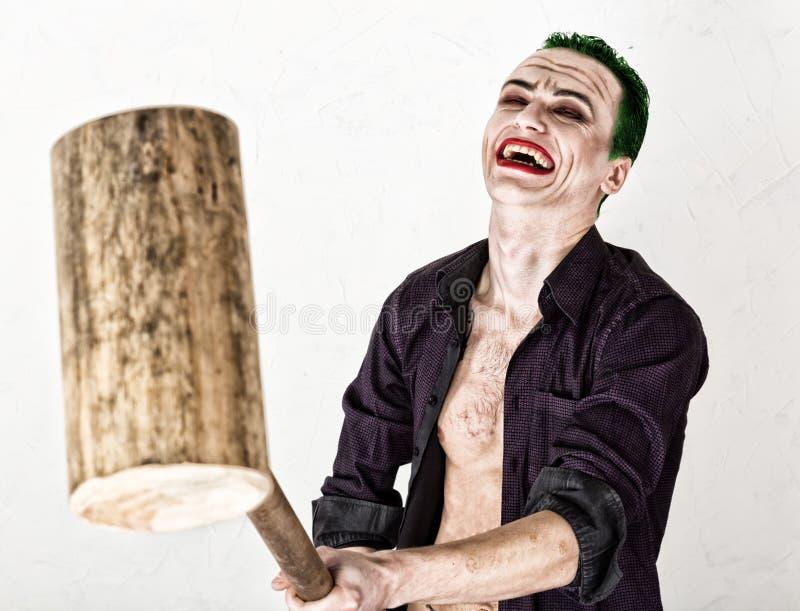 Kerel met gek jokergezicht, groen haar en idiotic glimlach carnaval kostuum holdingshamer voor veenmol royalty-vrije stock foto