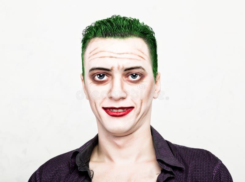 Kerel met gek jokergezicht, groen haar en idiotic smike carnaval kostuum stock afbeeldingen