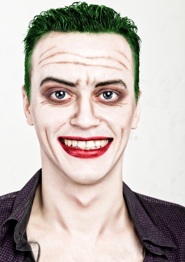 Kerel met gek jokergezicht, groen haar en idiotic smike carnaval kostuum stock fotografie