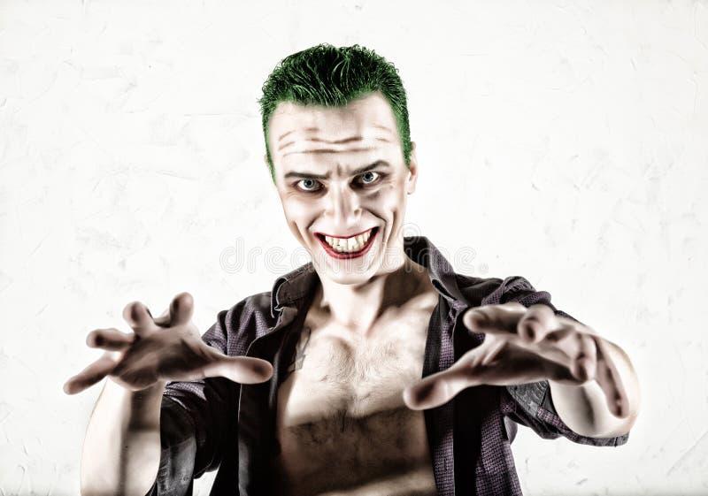 Kerel met gek jokergezicht, groen haar en idiotic smike carnaval kostuum royalty-vrije stock afbeeldingen