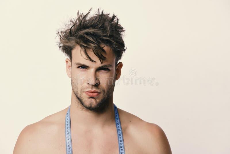 Kerel met sexy die gezichtsuitdrukking op lichtgrijze achtergrond wordt geïsoleerd Mens met lange blauwe metende band rond mannet stock foto's