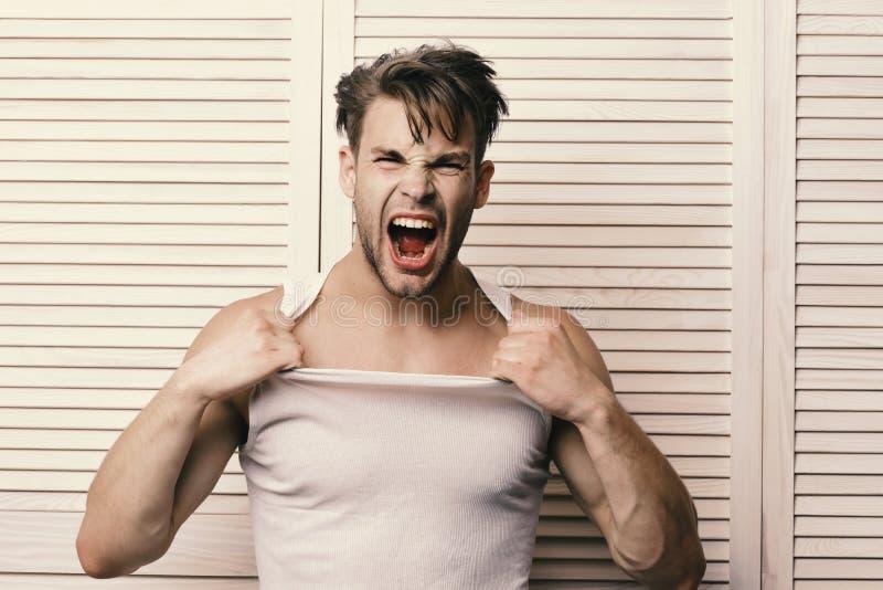 Kerel met sterke spieren en varkenshaar in wit mouwloos onderhemd Mens met eerlijk haar op lichte houten plankenachtergrond stock foto