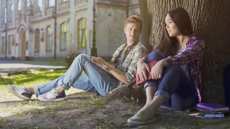 Kerel onder boom die meisjeszitting bekijken naast hem, liefde op het eerste gezicht gevoel stock afbeelding